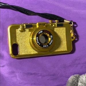 A gold camera case with a land yard